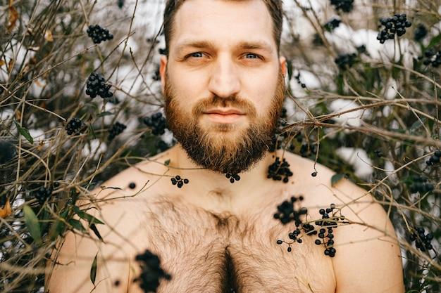 Ritratto di uomo nudo brutale allo zenzero con la barba in posa tra i cespugli