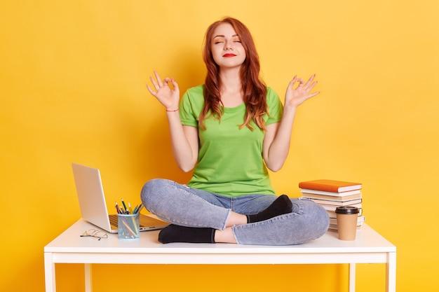 Ritratto di ragazza di zenzero seduto sulla scrivania con calma espressione facciale