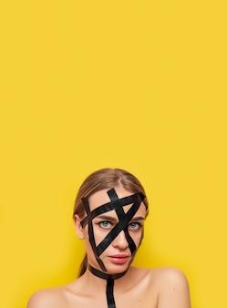 Ritratto di una ragazza in stile bdsm in nastro adesivo, moda, cosmetologia, sfondo giallo