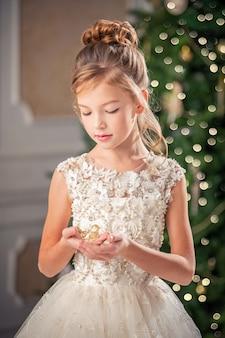 Ritratto di una ragazza in un bel vestito su uno sfondo di albero di natale