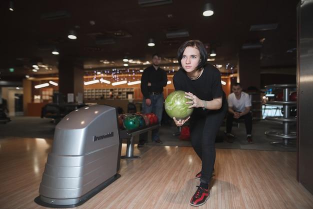 Ritratto di una ragazza prima di lanciare una palla da bowling nella scenetta. la ragazza gioca a bowling.