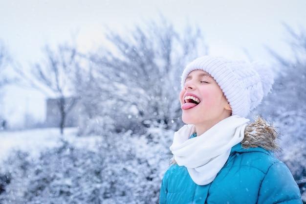 Ritratto di una ragazza in abiti invernali blu cattura i fiocchi di neve con la sua lingua nel parco.