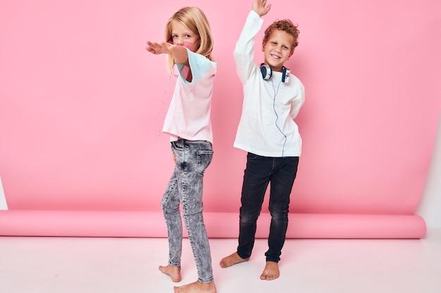 Ritratto di una ragazza e un ragazzo con le cuffie per l'intrattenimento che suonano il concetto di stile di vita dell'infanzia