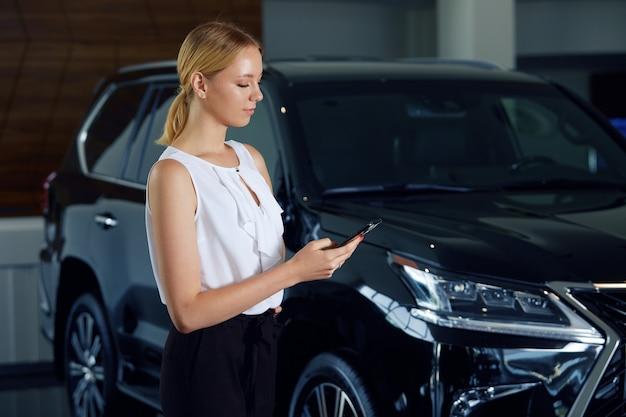 Ritratto di una ragazza in una concessionaria di auto con un telefono in mano sullo sfondo di un'auto