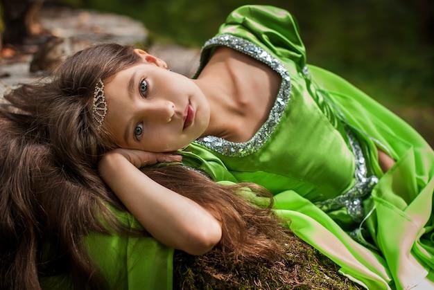 Ritratto di una ragazza in un abito da elfo da favola si siede sulle antiche rovine nella foresta