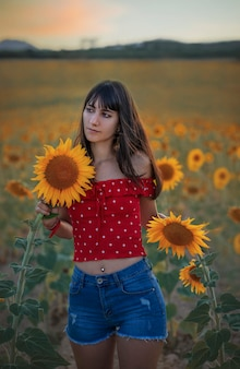 Ritratto di una ragazza in un campo di girasoli durante il tramonto.