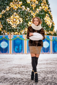 Ritratto di una ragazza in un cappotto di pelliccia sullo sfondo di un albero di natale.