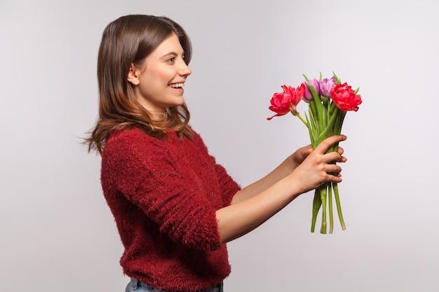 Ritratto di ragazza che dà bouquet di fiori e sorride eccitato. congratulazioni per le vacanze di primavera