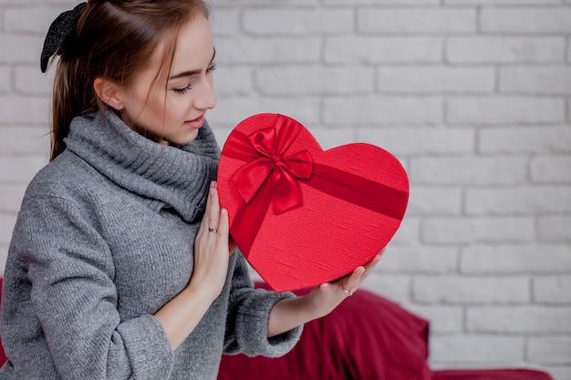 Ritratto di una ragazza in un maglione grigio con un contenitore di regalo rosso in forma di cuore che si siede nell'appartamento, concetto di san valentino, spazio della copia Foto Premium