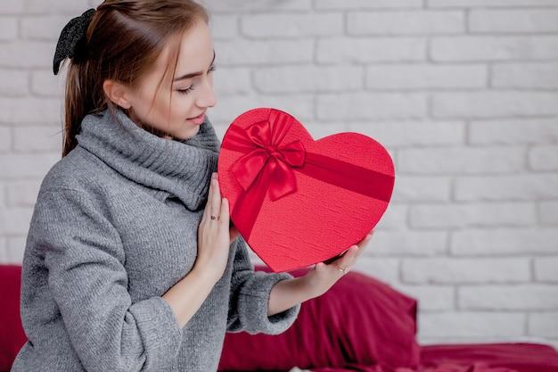 Ritratto di una ragazza in un maglione grigio con una confezione regalo rossa a forma di cuore. san valentino