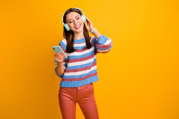 Ritratto di ragazza ascoltando musica in auricolari tenere telefono