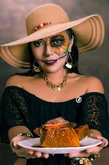 Ritratto di ragazza truccata da catrina che offre un dolce a base di zucca