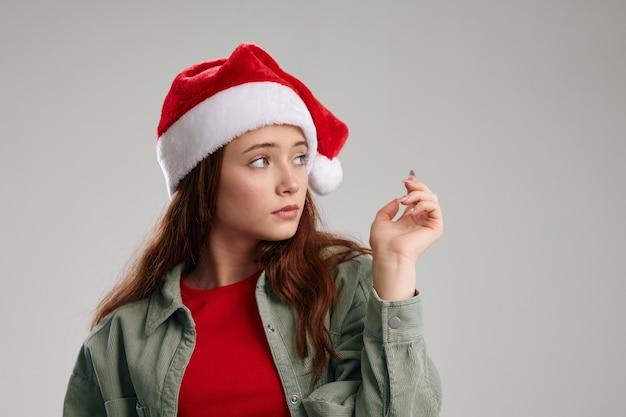 Ritratto di una ragazza in un cappello e una giacca di capodanno su uno sfondo grigio copy space