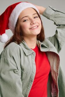 Ritratto di una ragazza con un cappello rosso con un pompon natale capodanno divertente. foto di alta qualità