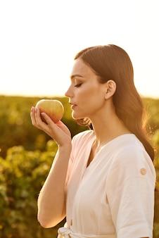 Ritratto di una ragazza in piedi di profilo con una mela in mano su uno sfondo di campo verde in una giornata di sole.