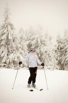Ritratto di una ragazza in piedi con gli sci e in posa contro montagne innevate e foreste