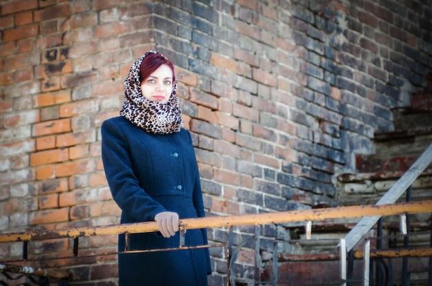 Ritratto di una ragazza in piedi sulle scale di una vecchia casa di mattoni