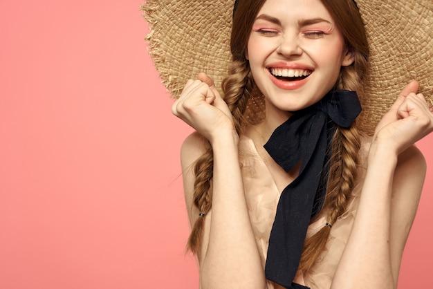 Ritratto di una ragazza in un cappello di paglia su uno sfondo rosa di close-up.