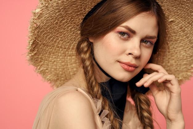 Ritratto di una ragazza in un cappello di paglia su uno sfondo rosa emozioni close-up bel viso modello trecce. foto di alta qualità