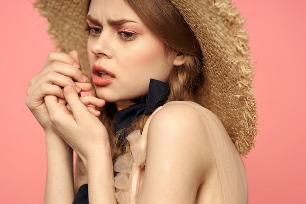 Ritratto di una ragazza in un cappello di paglia su uno sfondo rosa emozioni close-up bellissimo viso modello