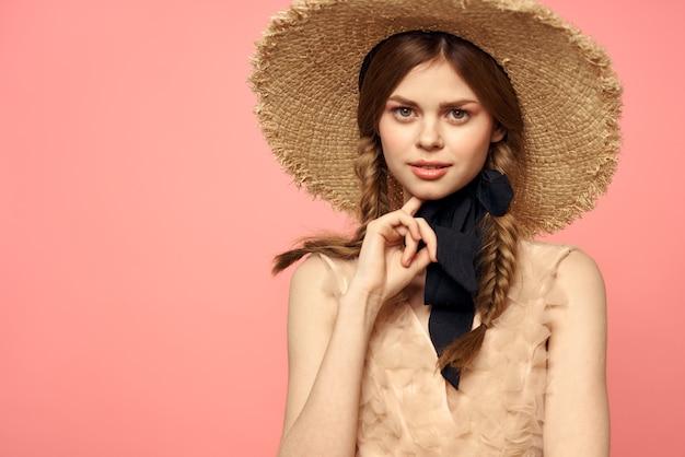 Ritratto di una ragazza in un cappello di paglia su un primo piano di emozioni di sfondo rosa