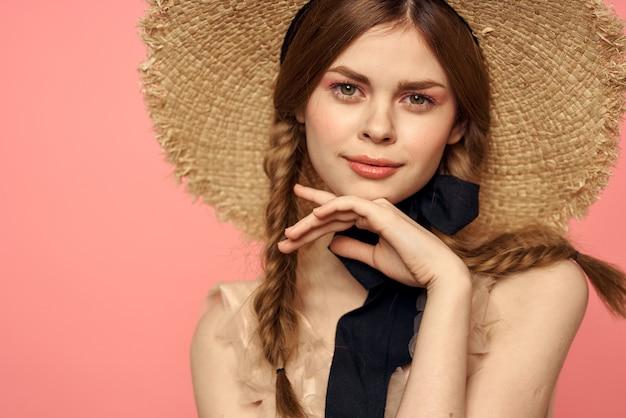 Ritratto di una ragazza in un cappello di paglia su un modello di viso bellissimo primo piano di emozioni rosa