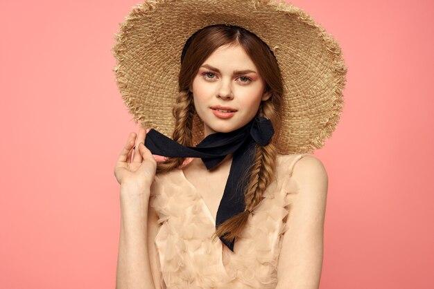 Ritratto di una ragazza con un cappello di paglia su una rosa