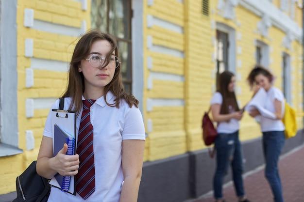 L'adolescente della studentessa del ritratto in vetri lega la maglietta bianca con lo zaino. edificio di mattoni gialli di sfondo, gruppo di studenti