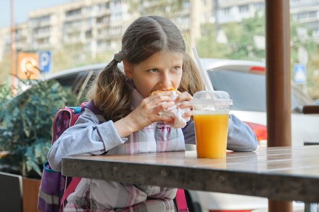 Ritratto di studentessa con zaino, mangiare hamburger con succo d'arancia