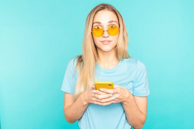 Il ritratto della ragazza usa il suo smartphone legge le notizie dei social media urla wow omg isolato su colore blu