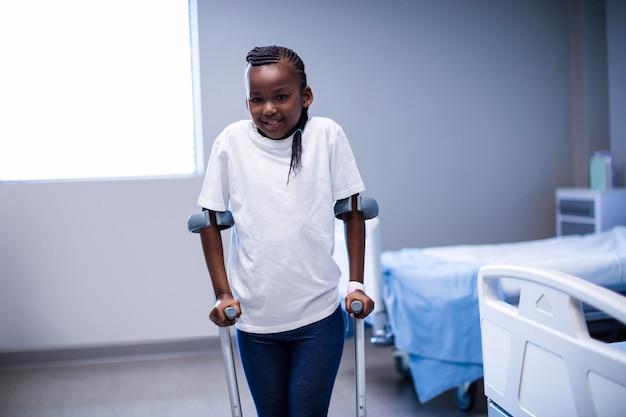 Ritratto della ragazza che cammina con le stampelle in reparto