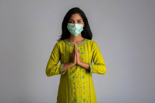 Ritratto di una ragazza che indossa una maschera medica facendo saluto con il gesto di namaste.