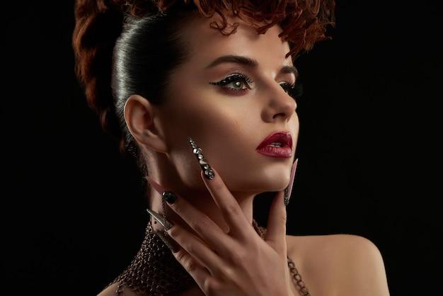 Ritratto di ragazza che indossa nail art e trucco luminoso.