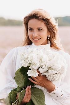 Ritratto di una ragazza in un abito bianco con un mazzo di fiori in estate nella natura nel campo