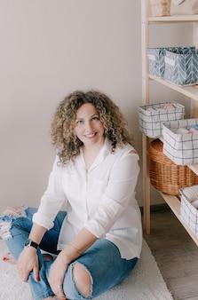 Ritratto di una ragazza con bei capelli ricci seduta sul pavimento in jeans e una camicia leggera. bel sorriso