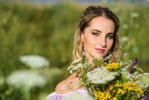 Ritratto di una ragazza con un mazzo di fiori di campo da vicino.