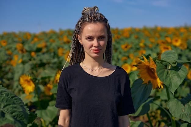 Ritratto di una ragazza con i dreadlocks che sta in mezzo a un luminoso campo di girasoli e guarda...