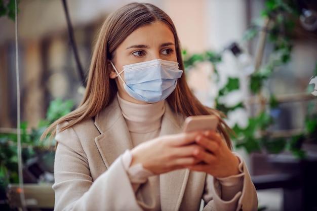 Ritratto di ragazza con la maschera per il viso seduto in un caffè all'aperto e utilizzando il telefono per l'e-banking.