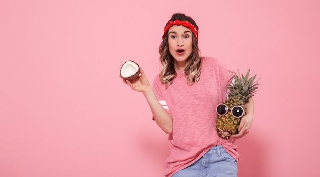 Ritratto di una ragazza con frutta su una parete rosa