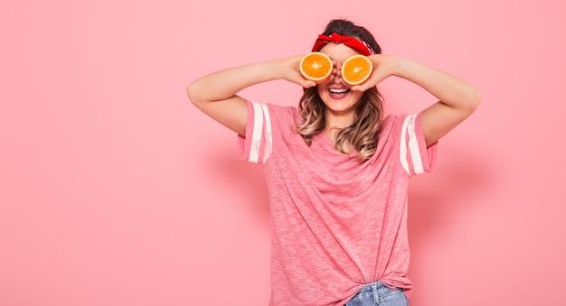 Ritratto di una ragazza con le arance in mano, su una parete rosa