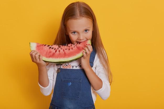 Ritratto di ragazza con un pezzo di anguria, sorrisi e mangiare gustosa anguria