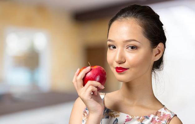 Ritratto della ragazza con la mela rossa isolata