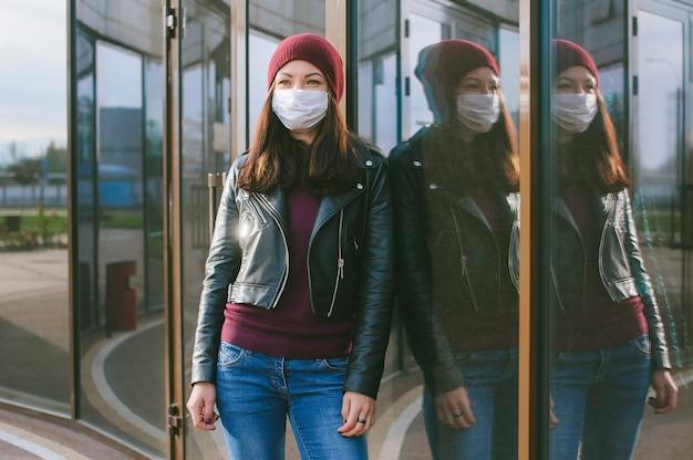 Ritratto di una ragazza con riflessi sul vetro di un edificio in una maschera medica. sullo sfondo del centro commerciale.