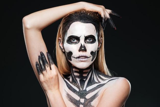 Ritratto di ragazza con trucco scheletro spaventato su sfondo nero