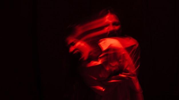 Ritratto di una ragazza con schizofrenia e disturbi mentali in una camicia bianca con luce rossa su sfondo nero