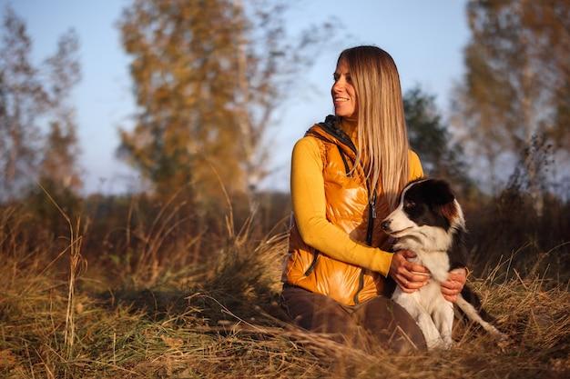 Ritratto di una ragazza in giallo e border collie su uno sfondo di natura.