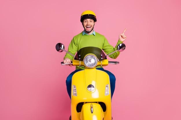 Ritratto di felice ragazzo allegro in sella a una moto che mostra annuncio