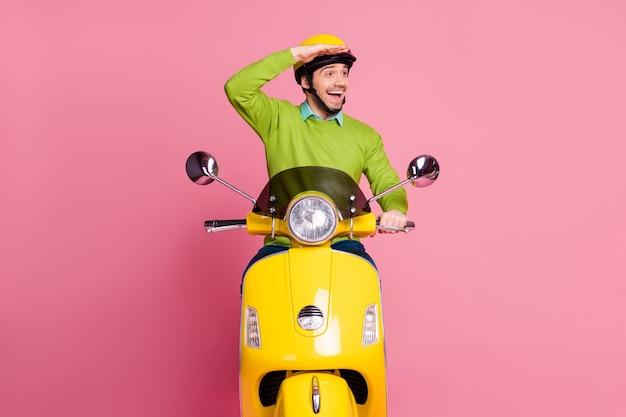 Ritratto di ragazzo amichevole felice che guida il lato di sguardo del ciclomotore