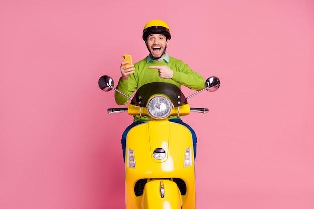 Ritratto di felice ragazzo in sella a una moto che mostra cellulare dito diretto
