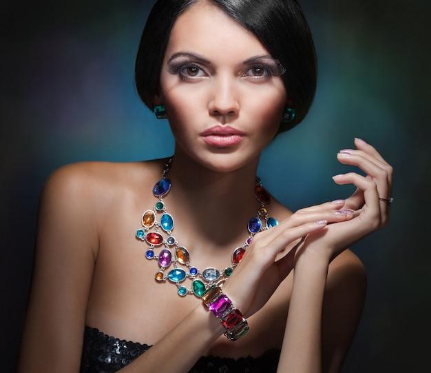 Ritratto di una ragazza affascinante con i capelli neri e una costosa collana di pietre preziose e colorate